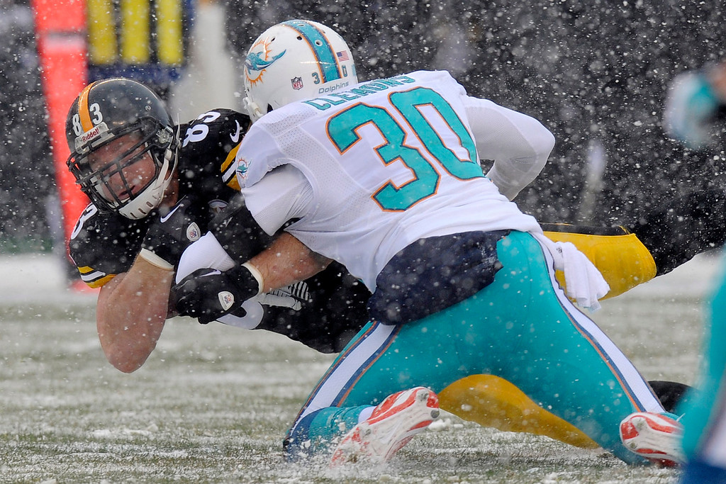 . Pittsburgh Steelers tight end Heath Miller (83) is tackled by Miami Dolphins strong safety Chris Clemons (30) after taking a pass from Pittsburgh Steelers quarterback Ben Roethlisberger (7) during the first half of an NFL football game in Pittsburgh, Sunday, Dec. 8, 2013. (AP Photo/Don Wright)