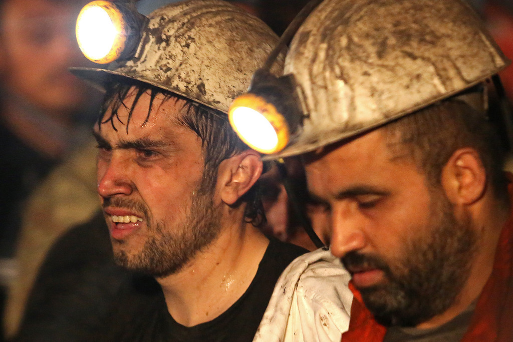 . A miner is helped by rescue workers and friends from the coal mine on May 14, 2014 in Soma, Manisa, Turkey.  (Photo by Ozgu Ozdemir/Getty Images)