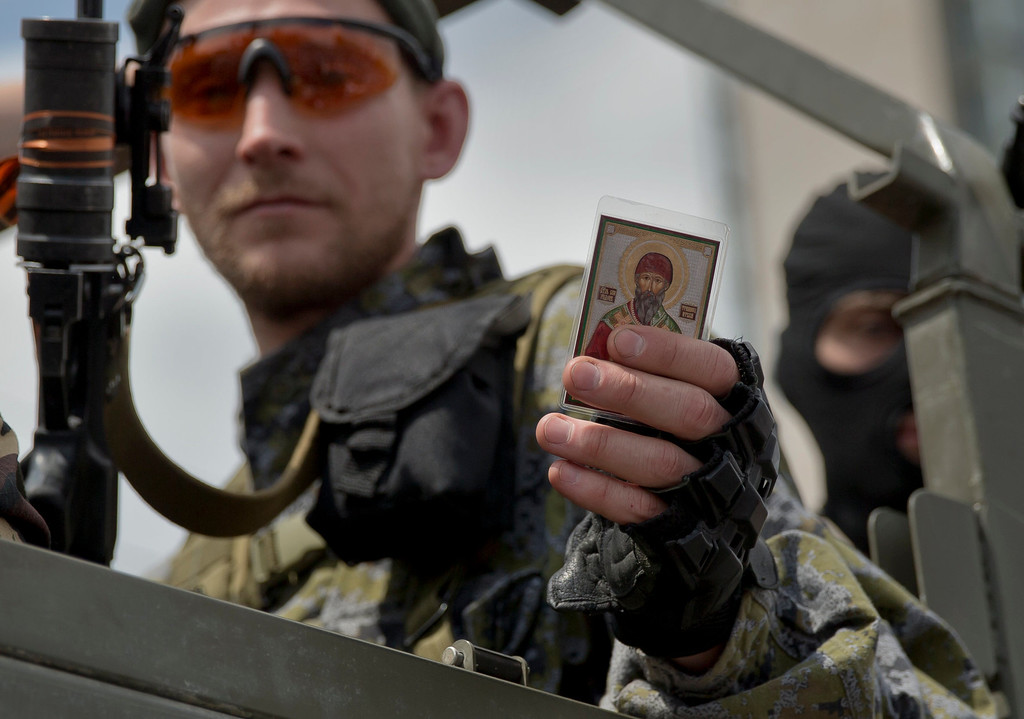 ". A Pro-Russian gunman holds an icon received from a woman in Lenin Square, Donetsk, Ukraine, Sunday, May 25, 2014. A convoy of an armored personnel carrier and seven trucks carrying several hundred heavily armed men drove through central Donetsk early Sunday afternoon and gunmen got out of the trucks, stood to attention and gave shots in the air in jubilation as a crowd of several thousand supporters cheered them and chanted: ""Heroes!\"". Ukraine\'s critical presidential election got underway Sunday under the wary scrutiny of a world eager for stability in a country rocked by a deadly uprising in the east. (AP Photo/Vadim Ghirda)"
