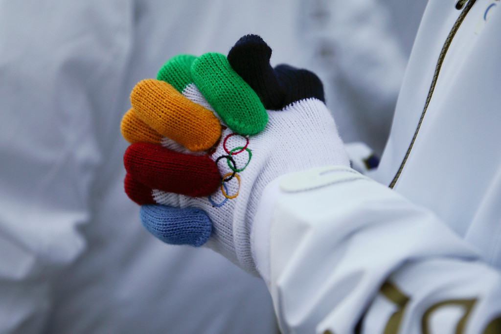 . An athlete from the Czech Republic wears a pair of gloves given to him as a gift during a welcome ceremony at the Mountain Olympic Village prior to the 2014 Winter Olympics, Wednesday, Feb. 5, 2014, in Krasnaya Polyana, Russia. (AP Photo/Jae C. Hong)
