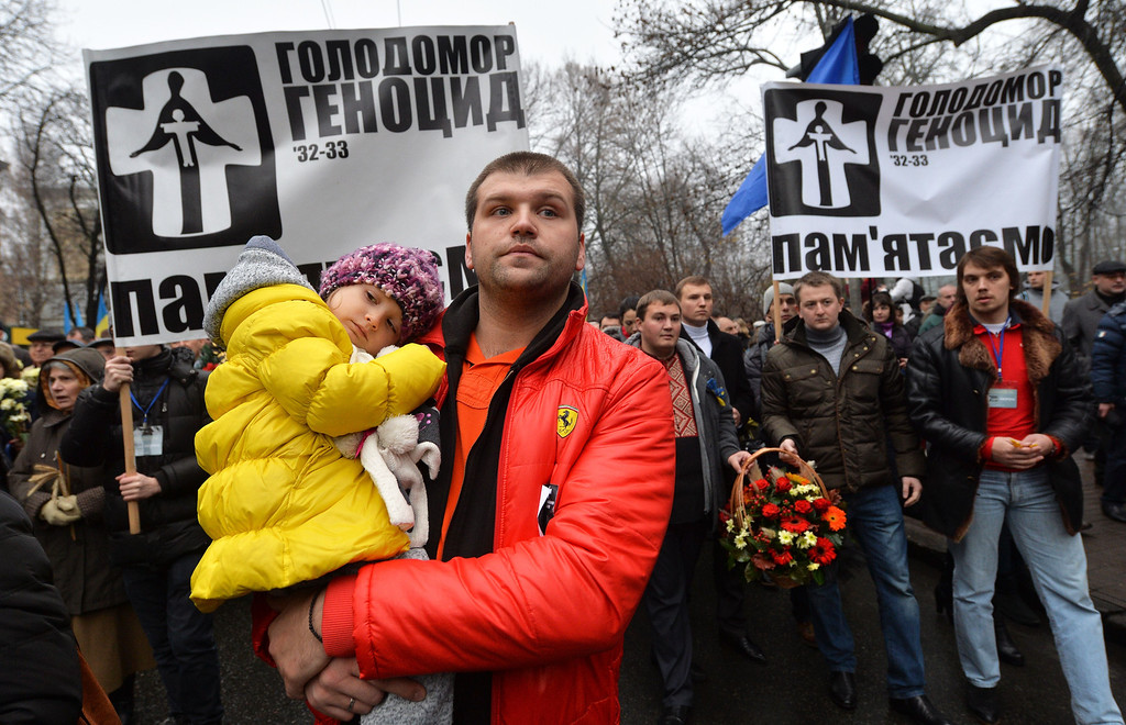. A man carries his daughter  on November 23, 2013 during a march of thousands in memory of the victims of the Holodomor famine before a ceremony at the Holodomor memorial in Kiev.  AFP PHOTO/ SERGEI SUPINSKY/AFP/Getty Images