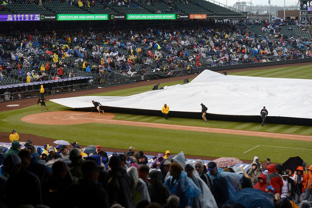 . Grounds crew pulls the tarp over the infield in the fifth inning during the fifth inning of the Colorado Rockies New York Yankees game May 9, 2013 at Coors Field. (Photo By John Leyba/The Denver Post)