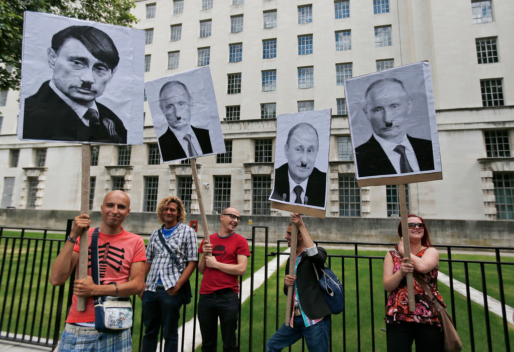 """. Activists holding placards depicting Russian President Vladimir Putin as Adolf Hitler, participate at a protest against Russia\'s new law on gays, in central London, Saturday, Aug. 10, 2013.  Hundreds of protesters called for the Winter 2014 Olympic Games to be taken away from Sochi, Russia, because of a new Russian law that bans \""""propaganda of nontraditional sexual relations\"""" and imposes fines on those holding gay pride rallies. (AP Photo/Lefteris Pitarakis)"""