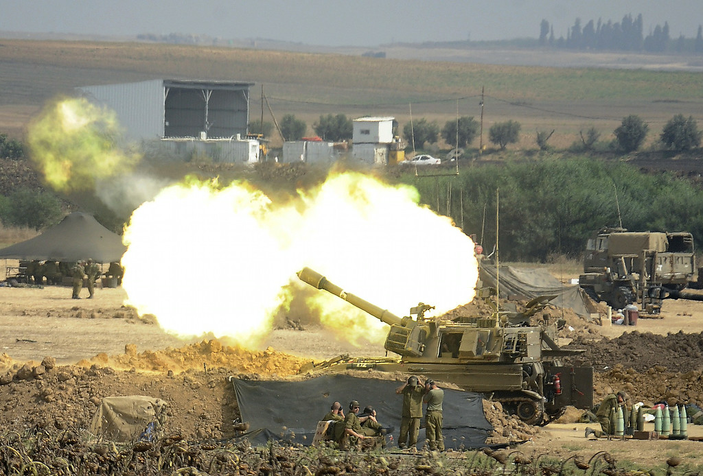 . An Israeli canon fires a 155mm shell towards targets in the Gaza Strip from their position along the border between Israel and the Hamas-controlled Gaza Strip on July 29, 2014. Bloodshed in war-torn Gaza surged on with dozens more Palestinians killed as the conflict raged into a fourth week and Iran accused Israel of genocide in the tiny enclave. AFP PHOTO/ DAVID BUIMOVITCH/AFP/Getty Images