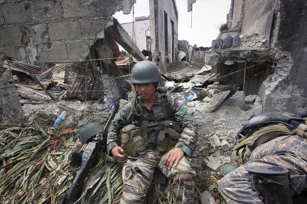 . A government trooper rests amidst the ruins at the site of a three-week standoff in Zamboanga city, southern Philippines, Saturday, Sept. 28, 2013. The deadly standoff between government troops and Muslim rebels who held nearly 200 people hostage ended with all of the captives safe, officials said Saturday. Defense Secretary Voltaire Gazmin said only a handful of Moro National Liberation Front rebels remained in hiding and were being hunted by troops in the coastal outskirts of Zamboanga city, adding authorities were trying to determine if rebel commander Habier Malik, who led the Sept. 9 siege, was dead. (AP Photo)
