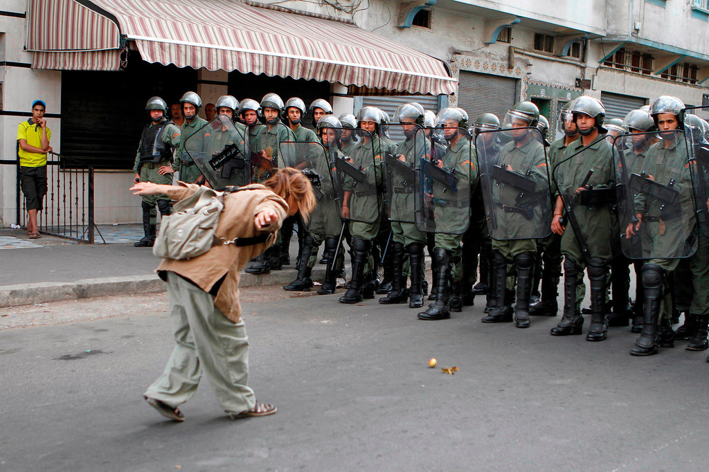 """. A pro-democracy demonstrator gestures at policemen during a protest organized by the \""""February 20 Movement\"""", who are demanding political reforms, in Casablanca May 29, 2011. REUTERS/Macao"""