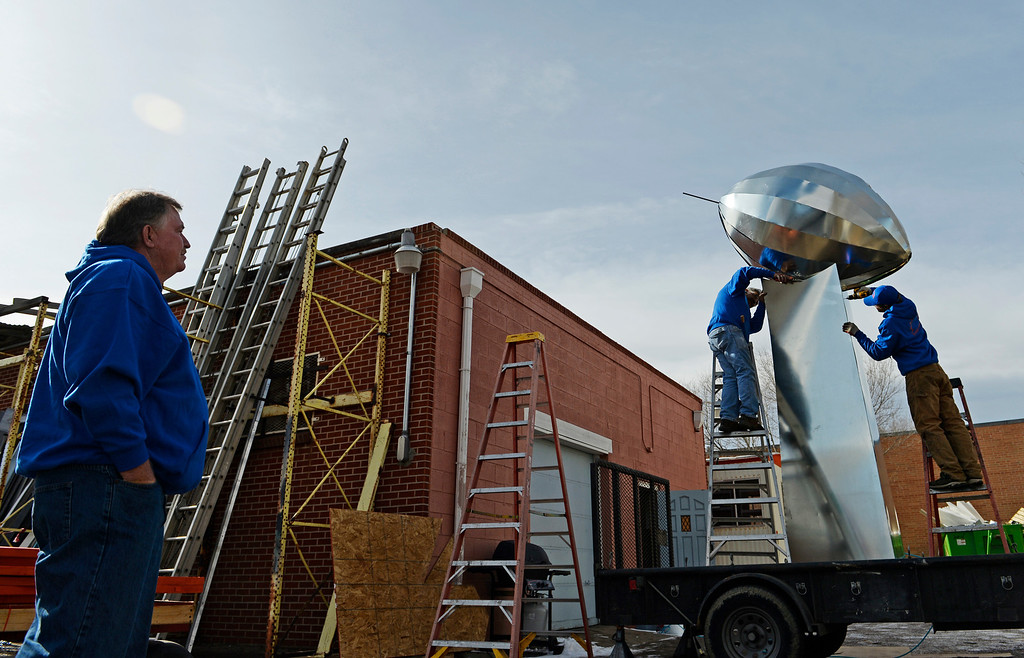 . Bob Schmitz, left, owner of Frontier Roofing System in east Denver, watches his crew work on a 14-foot Vince Lombardi Trophy, January, 26 2014. The owner is a huge Denver Broncos fan and wants the trophy to drive around downtown Denver, and to bring to his families Super Bowl party. Carlos Tovar, center, and John Darling put sheet metal on the side of the trophy. (Photo by RJ Sangosti/The Denver Post)