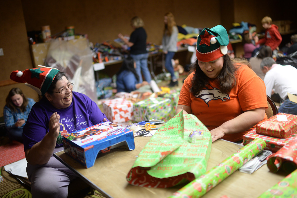 """. DENVER, CO. DECEMBER 21: Barbara Tolmich of Denver, left, and her daughter Leanna are wrapping Christmas gift during the annual Father Woody Christmas Party in Denver, Colorado December 21, 2013. In advance of handing out 5,000 gifts, volunteers are doing a \""""wrapping party\"""" at the Sheraton Denver Downtown Hotel. (Photo by Hyoung Chang/The Denver Post)"""