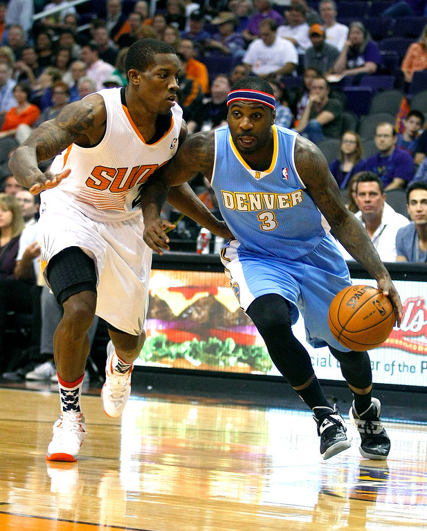 . Denver Nuggets point guard Ty Lawson (3), right, drives past Phoenix Suns point guard Eric Bledsoe (2) in the first quarter during an NBA basketball game on Friday, Nov. 8, 2013, in Phoenix. (AP Photo/Rick Scuteri)