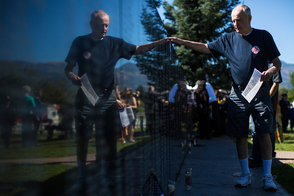 . Jack Sawin of Chicago, Ill. looks for a name on the IAFF Fallen Firefighters Memorial Wall before the start of the annual IAFF Fallen Fire Fighter Memorial at Memorial Park in Colorado Springs, Colorado on Saturday, Sept. 21, 2013.(AP Photo/The Gazette, Kent Nishimura)