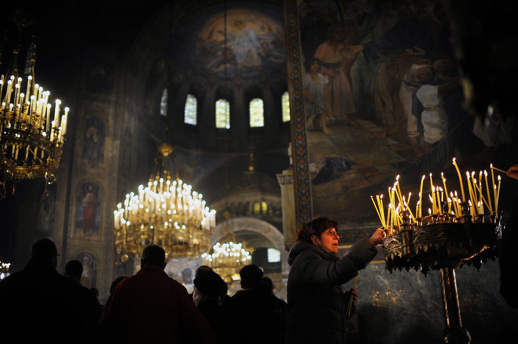 . A woman lights a candle during a Christmas mass in the golden-domed Alexander Nevsky cathedral in central Sofia on December 25, 2013. Bulgaria, unlike some other fellow Orthodox countries, celebrates Christmas on December 25.    NIKOLAY DOYCHINOV/AFP/Getty Images