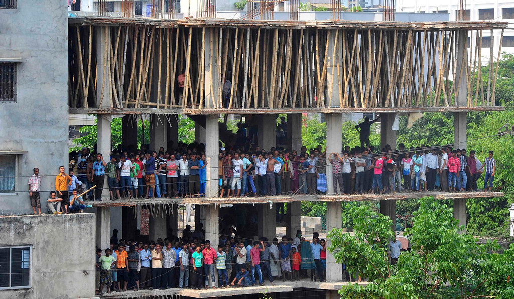 . People gather in an under-construction building to watch the rescue operation of the collapsed Rana Plaza building, in Savar, 30 km (19 miles) outside Dhaka April 27, 2013. Two factory bosses and two engineers were detained in Bangladesh on Saturday, three days after the collapse of a building where low-cost garments were made for Western brands killed at least 352 people. More were being pulled alive from the rubble at the building, where police said as many as 900 people were still missing in Bangladesh\'s worst ever industrial accident. REUTERS/Stringer