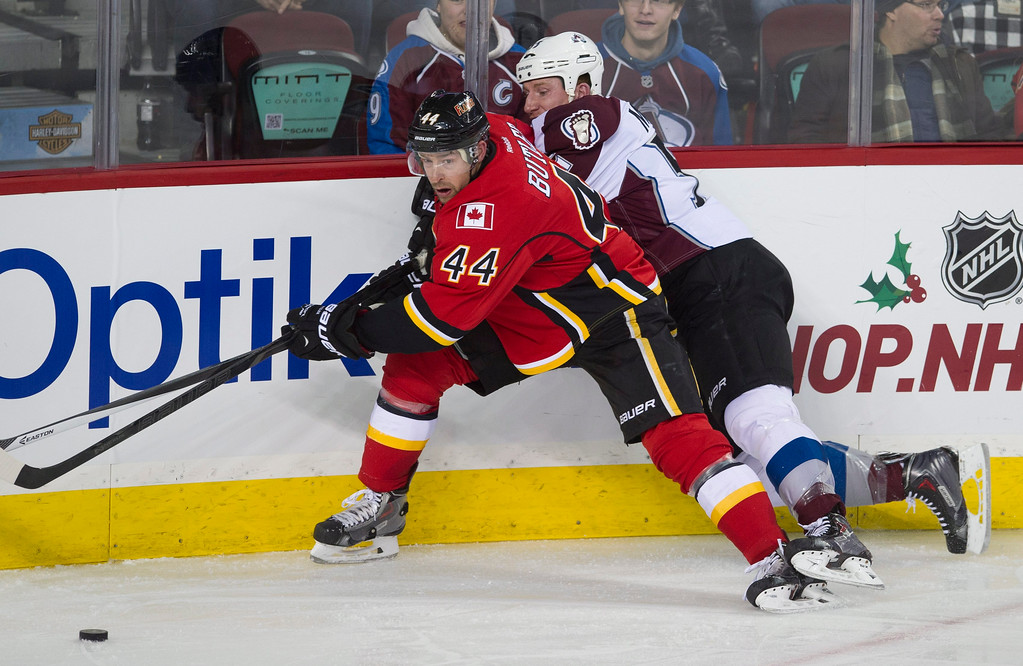 . Colorado Avalanche\'s Cody McLeod, right, battles for the puck with Calgary Flames\' Chris Butler during the second period of an NHL hockey game, Friday, Dec. 6, 2013 in Calgary, Alberta. (AP Photo/The Canadian Press, Larry MacDougal)