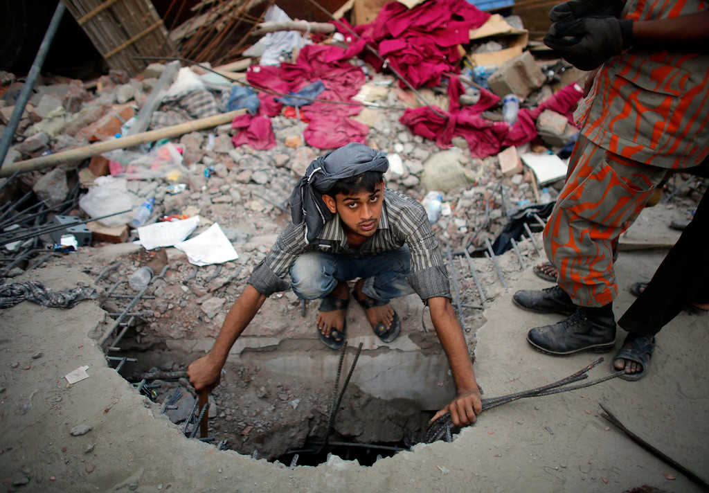 . A rescue worker tries to enter through a hole in an effort to rescue garment workers who were trapped in the Rana Plaza building which collapsed, in Savar, 30 km (19 miles) outside Dhaka April 24, 2013.  REUTERS/Andrew Biraj