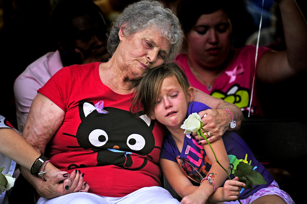 . Marlene Knobbe, grandmother of Micayla Medek, killed in the movie theater shooting, consoles family member Rachel Vigil at a community memorial for the victims of the shooting at the Aurora Municipal Center on Sunday, July 22, 2012. AAron Ontiveroz, The Denver Post