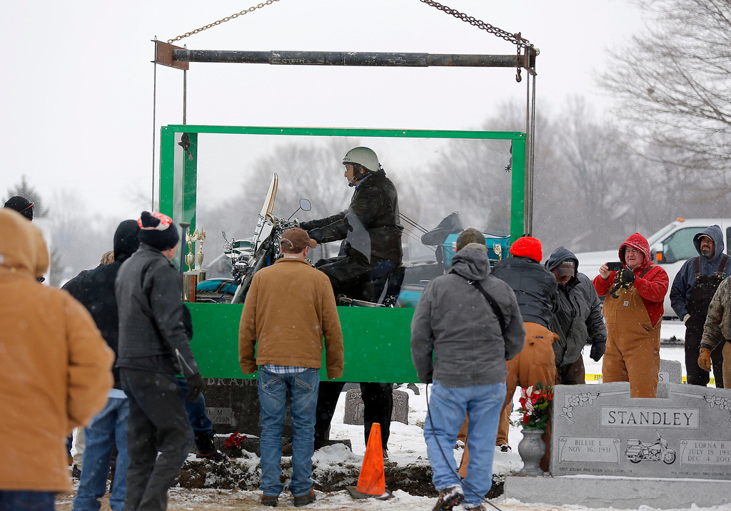 . The body of Bill Standley, secured to his 1967 Harley Davidson, rests inside a plexiglass box before being lowered into the ground at the cemetery in Mutual, Ohio on Friday, Jan. 31, 2014.   (AP Photo/Columbus Dispatch, Jonathan Quilter)