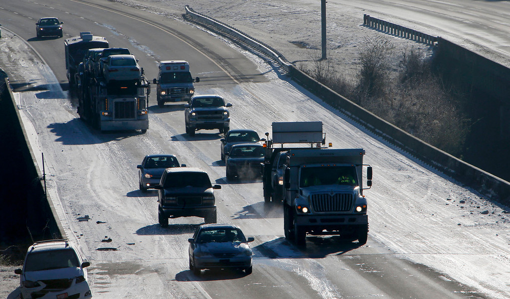 . Vehicles make their way over an icy interstate 20 bridge Thursday, Jan. 30, 2014 in Leeds, Ala. Hundreds of vehicles still litter the roadways as icy conditions and temperatures well below the freeing mark still exist.   (AP Photo/Hal Yeager)