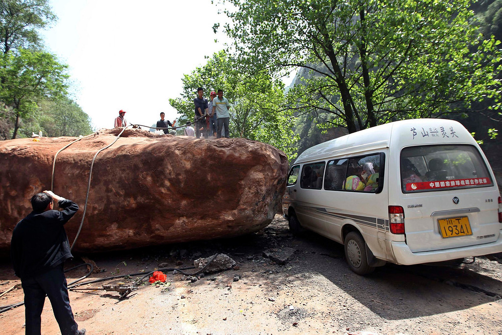 . People stand near a van on a road blocked by a large rock after a strong 6.6 magnitude earthquake, at Longmen village, Lushan county, Ya\'an, Sichuan province April 20, 2013. The earthquake hit a remote, mostly rural and mountainous area of southwestern China\'s Sichuan province on Saturday, killing at least 102 people and injuring about 2,200 close to where a big quake killed almost 70,000 people in 2008. REUTERS/Stringer