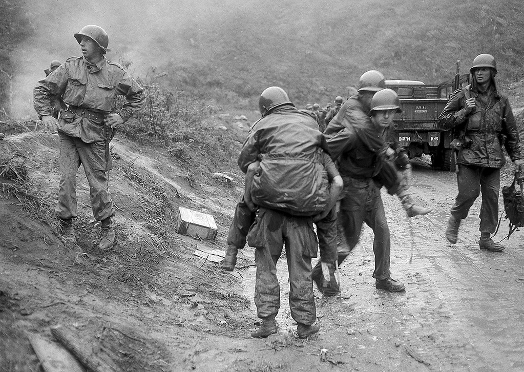 . American soldiers are carried on the backs of other GI\'s from Heartbreak Ridge through the rain to an aid station just behind the front lines in South Korea during the Korean War.  The 2nd Division GI\'s, wounded in an ambush as they came off the Ridge for a two-day rest, had spent two weeks in the line during the height of the bloody battle on the east central front.  (AP Photo)