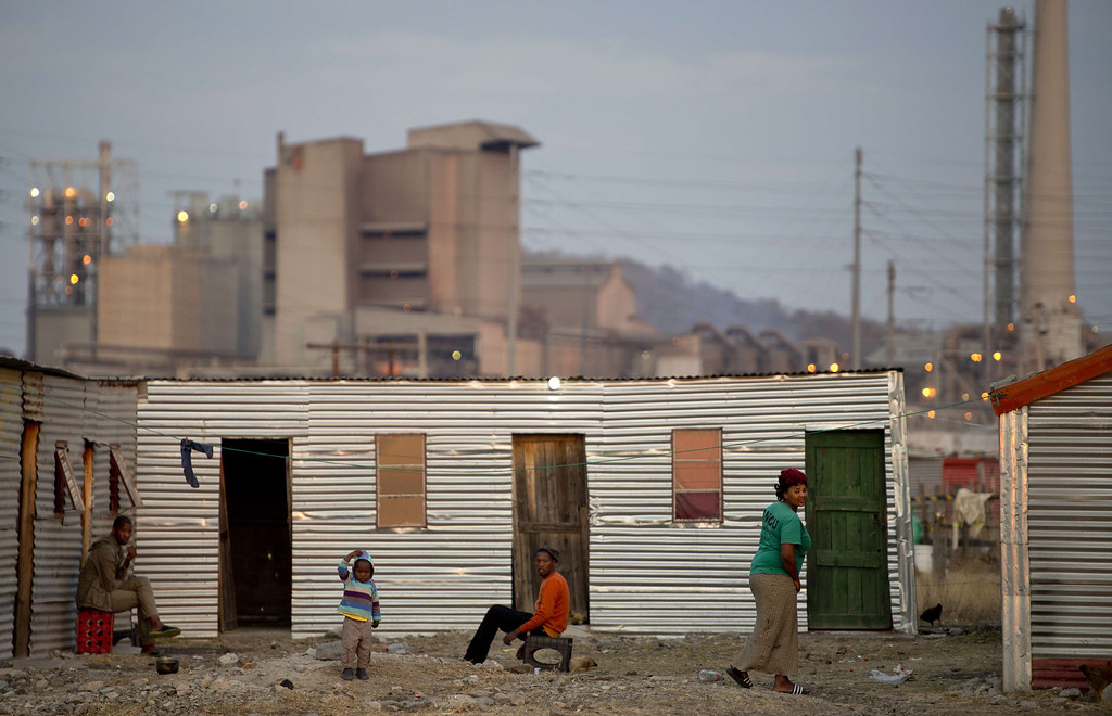 . People sit outside their shacks on July 9, 2013 in the Nkaneng shantytown next to the platinum mine, run by British company Lonmin, in Marikana. On August 16, 2012, police at the Marikana mine open fire on striking workers, killing 34 and injuring 78, during a strike was for better wages and living conditions. Miners still live in dire conditions despite a small wage increase. ODD ANDERSEN/AFP/Getty Images