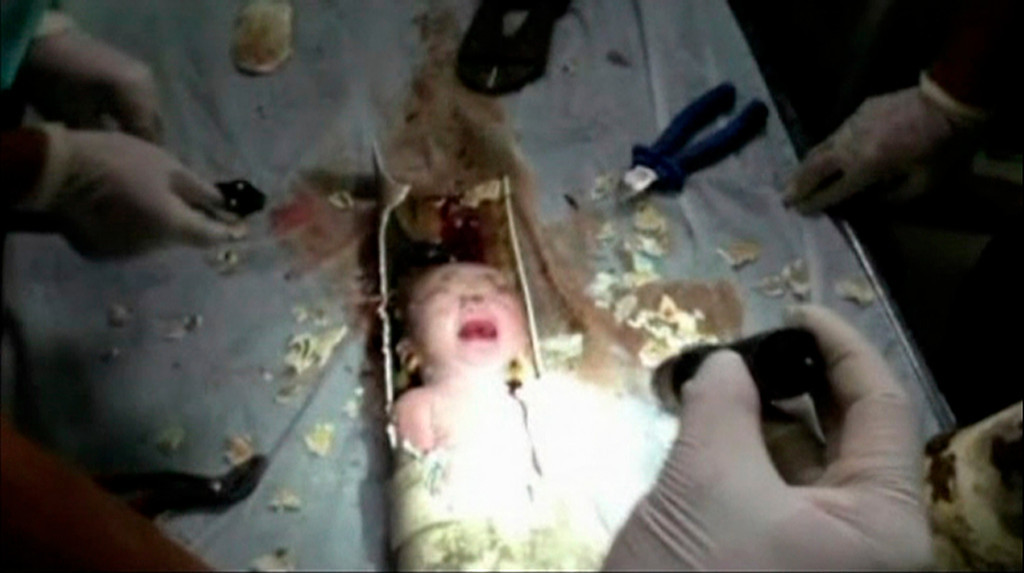 . An abandoned newborn baby boy is seen in a sewage pipe following his rescue, in this still image taken from video, in Jinhua city, Zhejiang province May 25, 2013.  REUTERS/Local Firefighter Handout via CCTV/Reuters TV