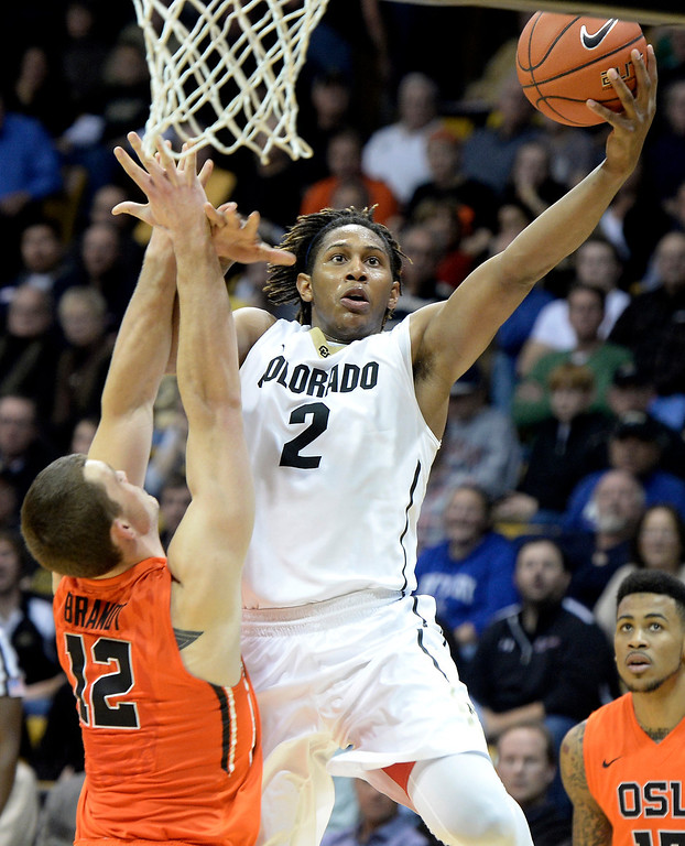 . Colorado\'s Xavier Johnson takes a shot over the defense of Angus Brandt during an NCAA game against Oregon State on Thursday, Jan. 2, at the Coors Event Center in Boulder.Jeremy Papasso/ Camera