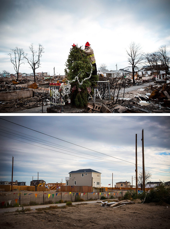 """. NEW YORK, NY - DECEMBER 25: (top)  Edward \""""Roaddawg\"""" Manley, a volunteer and honory firefighter with the Point Breeze Volunteer Fire Department, places a star on top of a Christmas tree December 25, 2012 in the Breezy Point neighborhood of the Queens borough of New York City.  NEW YORK, NY - OCTOBER 22: (bottom)  The same section of Breezy Point is shown October 22, 2013 in the Queens borough of New York City.  Hurricane Sandy made landfall on October 29, 2012 near Brigantine, New Jersey and affected 24 states from Florida to Maine and cost the country an estimated $65 billion.  (Photos by Andrew Burton/Getty Images)"""