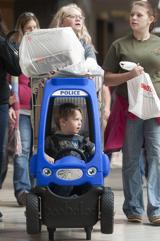 . Three-year-old Bradley Clay rides in the police car shopping cart at River Ridge mall as his mother Leanne Peade pushes him from behind a stack of purchases Friday, Nov. 29, 2013 in Lynchburg, Va. Black Friday, the day after Thanksgiving, is typically the nation\'s biggest shopping day of the year. (AP Photo/The News & Advance, Sam O\'Keefe)