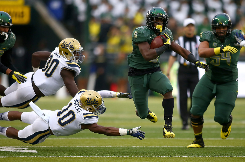 . EUGENE, OR - OCTOBER 26:  Byron Marshall #9 of the Oregon Ducks runs for a touchdown past Fabian Moreau #10 and Myles Jacks #30 of the UCLA Bruins on October 26, 2013 at the Autzen Stadium in Eugene, Oregon.  (Photo by Jonathan Ferrey/Getty Images)