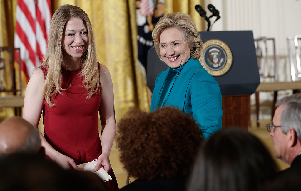 . Former U.S. Secretary of State Hillary Clinton (R) and her daughter Chelsea (L)  greet guests before U.S. President Barack Obama awarded former U.S. President Bill Clinton the Presidential Medal of Freedom in the East Room at the White House on November 20, 2013 in Washington, DC.   (Photo by Win McNamee/Getty Images)