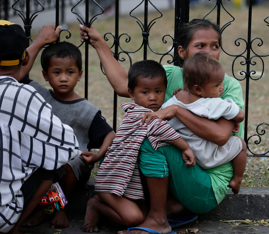 . Residents sitting in the open ground cling to a railing following an aftershock from the 7.2-magnitude earthquake that hit Cebu city in central Philippines Tuesday, Oct. 15, 2013. (AP Photo/Bullit Marquez)
