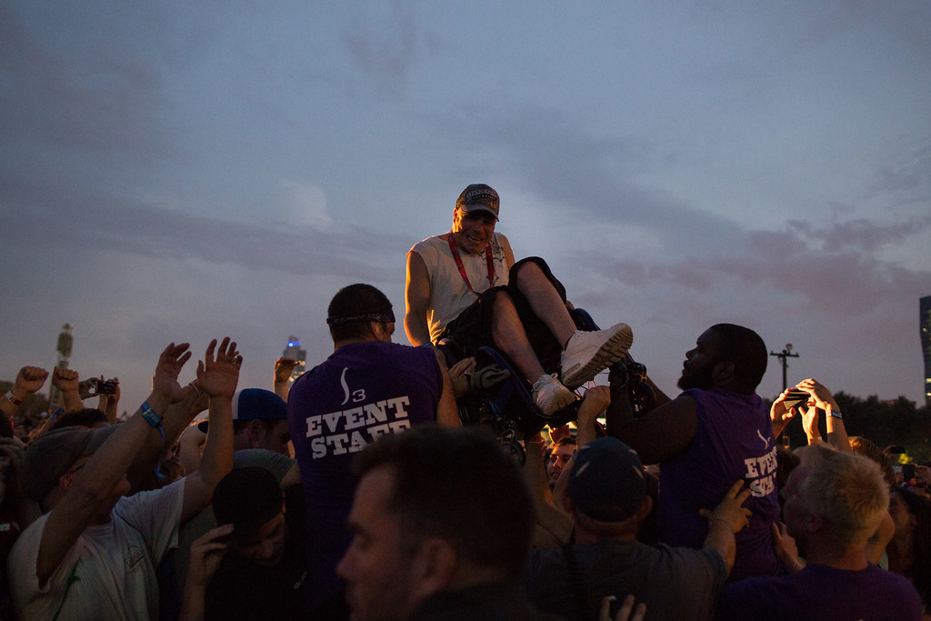 . A crowd surfer in a wheel chair is helped over the barricade while the band Nine Inch Nails performs at the Lollapalooza Festival in Chicago, Friday, Aug. 2, 2013. The more than two-decade-old festival opens Friday in Chicago\'s lakefront Grant Park. (AP Photo/Scott Eisen)