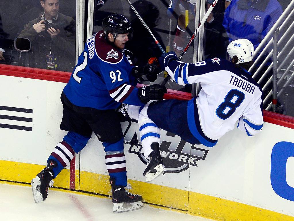 . Gabriel Landeskog (92) of the Colorado Avalanche checks Jacob Trouba (8) of the Winnipeg Jets during the second period as the Avs hosted the Jets at the Pepsi Center in Denver on Sunday, December 29, 2013. (Photo by AAron Ontiveroz/The Denver Post)