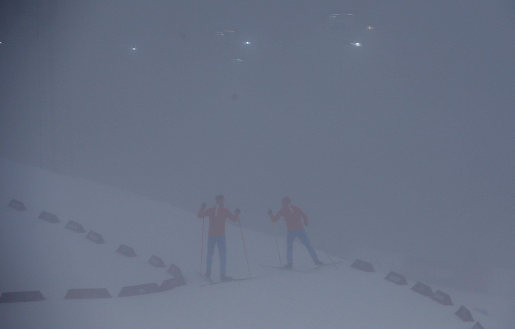 . Athletes ski through the fog as  the men\'s biathlon 15K mass start race has been postponed due to the lack of visibility at the 2014 Winter Olympics, Sunday, Feb. 16, 2014, in Krasnaya Polyana, Russia. (AP Photo/Gregorio Borgia)