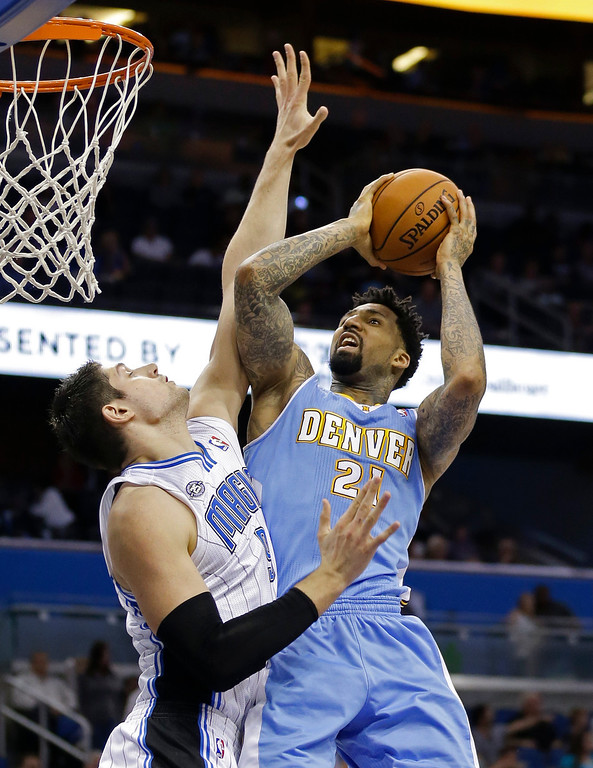 . Orlando Magic\'s Nikola Vucevic, left, fouls Denver Nuggets\'s Wilson Chandler, right, as he goes up for a shot during the first half of an NBA basketball game in Orlando, Fla., Wednesday, March 12, 2014. (AP Photo/John Raoux)