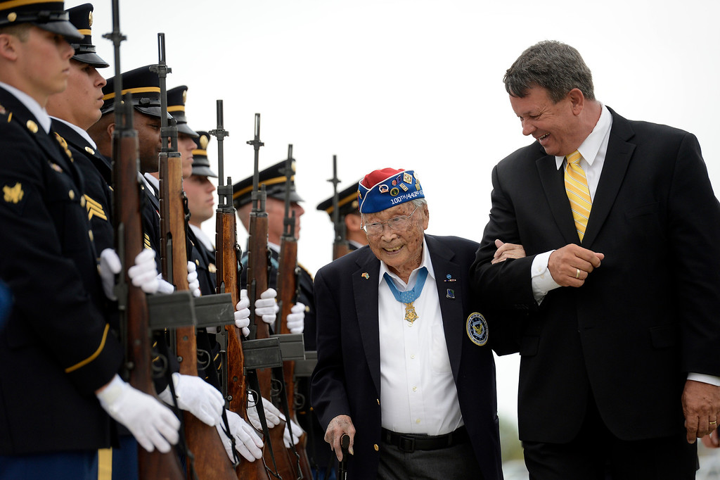 . Rick Carandall escorts 92-year-old George Sakato years-old back to his seat while walking past the Buckley Air Force Base Honor Guard during the Colorado Freedom Memorial dedication May 26, 2013 in Aurora. Private George T. Sakato distinguished himself by extraordinary heroism in action on 29 October 1944, on hill 617 in the vicinity of Biffontaine, France. After his platoon had virtually destroyed two enemy defense lines, during which he personally killed five enemy soldiers and captured four, his unit was pinned down by heavy enemy fire. (Photo By John Leyba/The Denver Post)