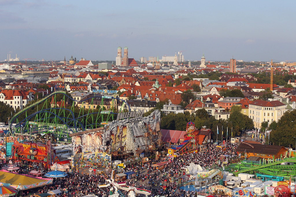 """. General view with Munich\'s Frauenkirche \""""Cathedral of Our Dear Lady\"""" in the background during day 1 of the Oktoberfest 2013 beer festival at Theresienwiese on September 21, 2013 in Munich, Germany. The Munich Oktoberfest, which this year will run from September 21 through October 6, is the world\'s largest beer fest and draws millions of visitors.  (Photo by Alexander Hassenstein/Getty Images)"""