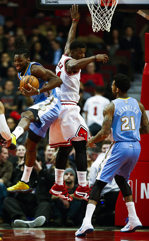 . Denver Nuggets forward Kenneth Faried (L) grabs a rebound  behind Chicago Bulls guard Jimmy Butler (C) as Denver Nuggets forward Wilson Chandler (R) watches in the first half of their NBA game at the United Center in Chicago, Illinois, USA, 21 February 2014  EPA/TANNEN MAURY