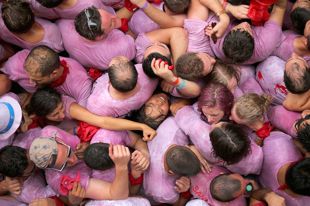 . A woman gets crushed as thousands of revellers sing and dance during the opening and the firing of the  \'Chupinazo\' rocket which starts the 2014 Festival of the San Fermin Running of the Bulls on July 6, 2014 in Pamplona, Spain. The annual Fiesta de San Fermin, made famous by the 1926 novel of US writer Ernest Hemmingway entitled \'The Sun Also Rises\', involves the daily running of the bulls through the historic heart of Pamplona to the bull ring.  (Photo by Christopher Furlong/Getty Images) *** BESTPIX ***