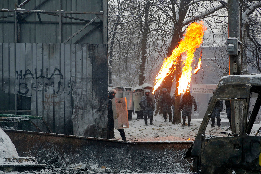 . Protesters throw molotov cocktails during clashes with police in central Kiev, Ukraine, early Wednesday, Jan. 22, 2014.   (AP Photo/Sergei Grits)