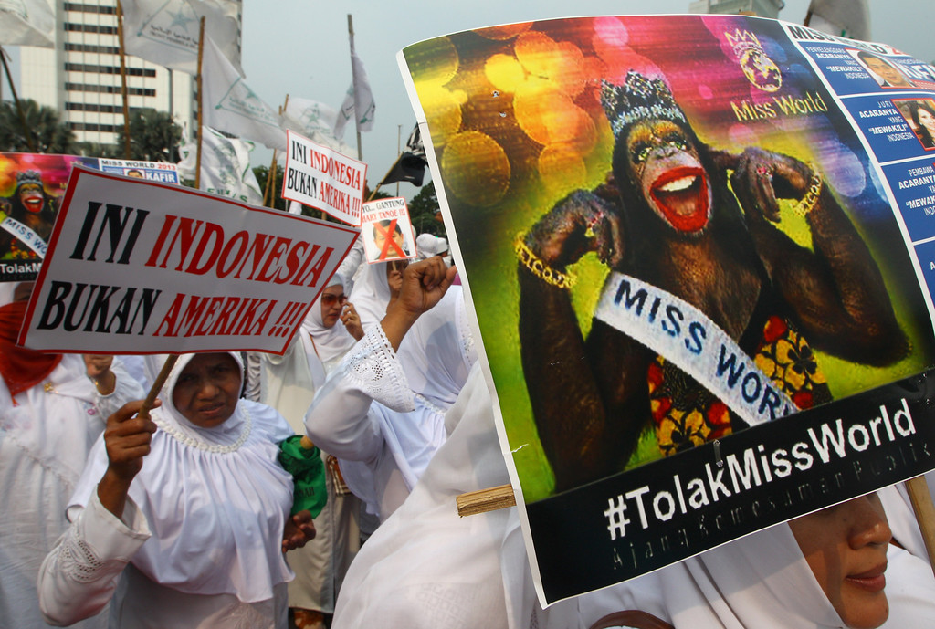 . In this Friday, Sept. 6, 2013 photo, Muslim women hold posters reading: Indonesia is not America, left, and Reject Miss World, during a protest demanding the cancellation of the Miss World pageant, in Jakarta, Indonesia. Most would expect a little backstage drama when dealing with beauty queens from 131 countries all vying for the coveted Miss World crown and sash, but this year\'s hair pulling and name calling has come in a different form with host country Indonesia caving into Muslim hardliners threatening to hijack the competition. (AP Photo/Dita Alangkara)