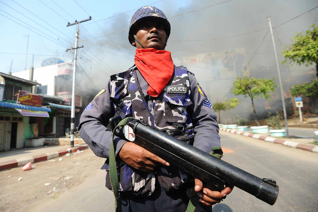 . A policeman stands guard in a street in riot-hit Meiktila, central Myanmar on March 22, 2013. Myanmar declared a state of emergency on March 22 for a riot-hit town where 20 people have been killed in Buddhist-Muslim violence that has sparked fears of spreading unrest.   AFP PHOTO/ Soe Than  WIN/AFP/Getty Images