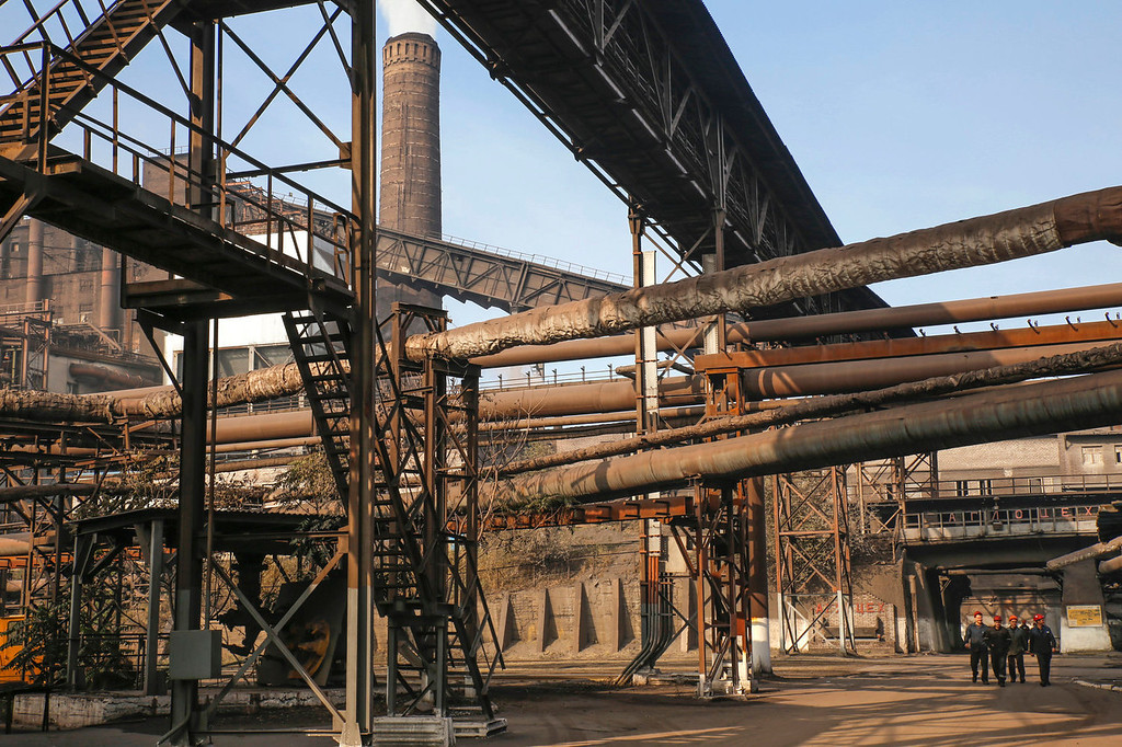 . Employees walk under pipes and metal structures at the Zaporizhstal steel plant, owned and operated by Metinvest BV, at their site in Zaporizhzhya, Ukraine, on Monday, Oct. 14, 2013. Metinvest BV, Ukraine\'s largest steelmaker, last year acquired 49.9% in steelmaker Zaporizhstal a manufacturer of semi-finished steel products, including hot and cold-rolled plates and coils. Photographer: Vincent Mundy/Bloomberg