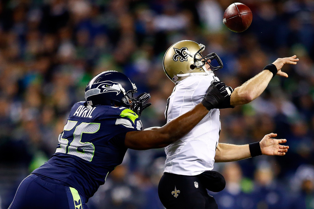 . Defensive end Cliff Avril #56 of the Seattle Seahawks knocks the ball from quarterback Drew Brees #9 of the New Orleans Saints in the first quarter during a game at CenturyLink Field on December 2, 2013 in Seattle, Washington.  (Photo by Jonathan Ferrey/Getty Images)