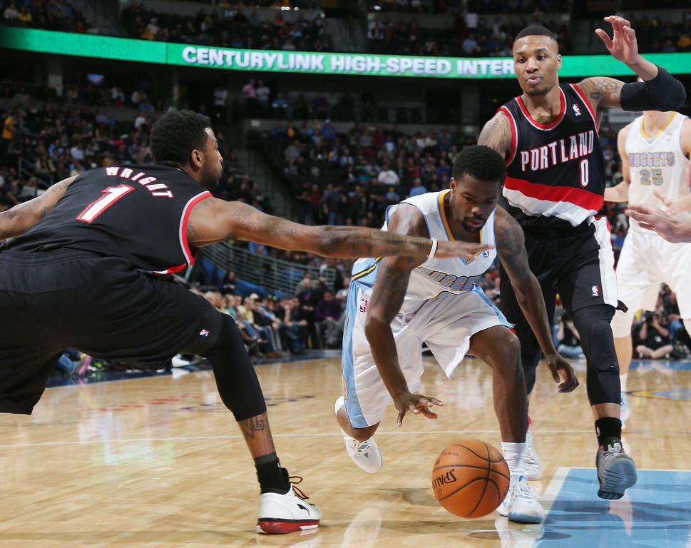 . Denver Nuggets guard Aaron Brooks, center, chases down a loose ball as Portland Trail Blazers forward Dorell Wright, left, and guard Damian Lillard cover in the third quarter of an NBA basketball game in Denver, Tuesday, Feb. 25, 2014. Portland won 100-95. (AP Photo/David Zalubowski)