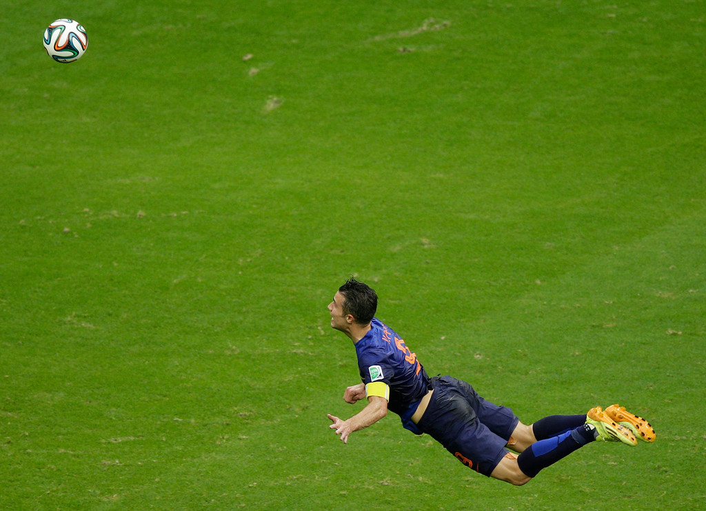 . Netherlands\' Robin van Persie heads the ball to score during the group B World Cup soccer match between Spain and the Netherlands at the Arena Ponte Nova in Salvador, Brazil, Friday, June 13, 2014.  (AP Photo/Christophe Ena)
