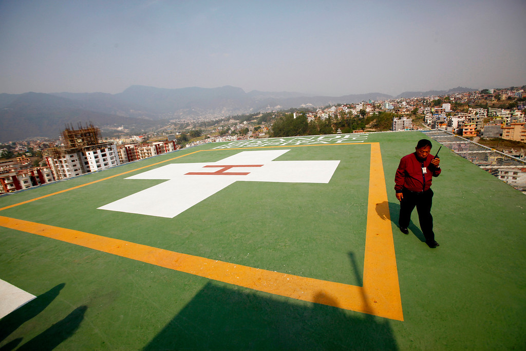 . A Nepalese security officer talks on a walky-talky while waiting for a helicopter to arrive with people injured by an avalanche, at the roof top of Grandy  hospital, in Katmandu, Nepal, Friday, April 18, 2014. An avalanche swept down a climbing route on Mount Everest early Friday, killing at least 12 Nepalese guides and leaving three missing in the deadliest disaster on the world\'s highest peak. (AP Photo/Niranjan Shrestha)