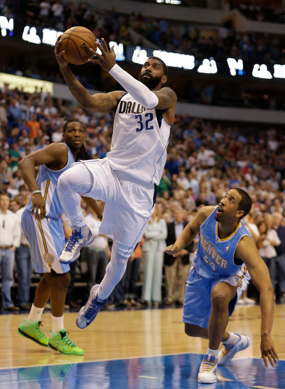 . Dallas Mavericks shooting guard O.J. Mayo (32) drives past Denver Nuggets point guard Andre Miller (24) and small forward Kenneth Faried (35) during overtime play of an NBA basketball game on Friday, April 12, 2013, in Dallas. The Mavericks won 108-105. (AP Photo/LM Otero)