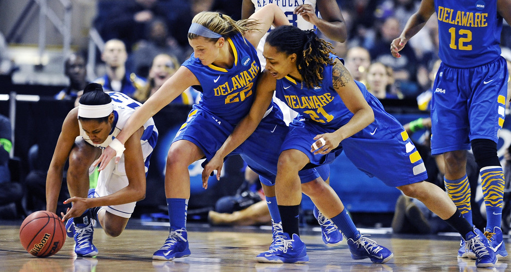 . Kentucky guard Bria Goss, left, grabs a loose ball against Delaware guards Lauren Carra (22) and Trumae Lucas (21) during the first half of a regional semifinal in the women\'s NCAA college basketball tournament in Bridgeport, Conn., Saturday, March 30, 2013. (AP Photo/Jessica Hill)