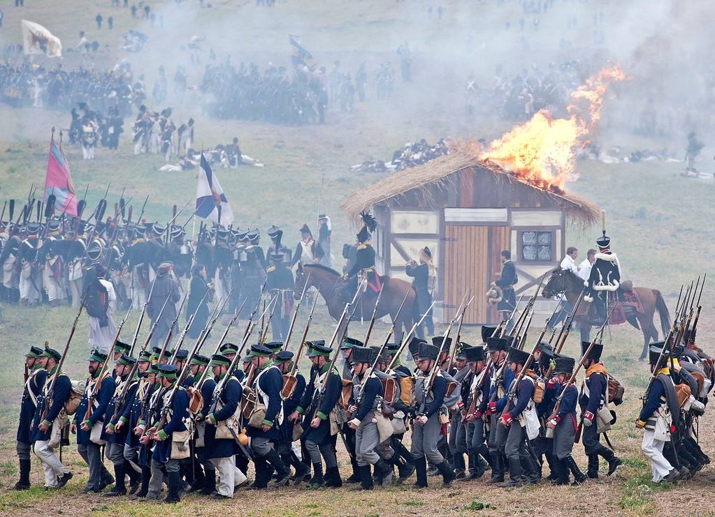 . Troops march in front of a burning house during the reconstruction of the Battle of the Nations at the 200th anniversary near Leipzig, central Germany, Sunday, Oct. 20, 2013. Some 6,000 members of military-historic associations from 24 countries took part in this performance. The Battle of Nations, from Oct. 16-19, 1813, was fought by the coalition armies of Russia, Prussia, Austria and Sweden against the French army of Napoleon. The battle decided that Napoleon had to retreat to France. (AP Photo/Jens Meyer)